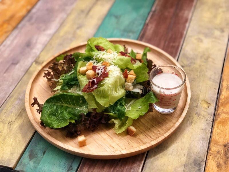 O bacon e o queijo cobriram na salada de Caesar no prato de madeira foto de stock