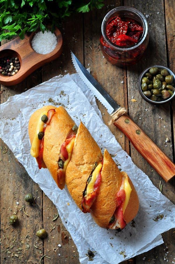 O baguette cozido enchido com bacon, queijo, sol-secou tomates e alcaparras fotos de stock royalty free