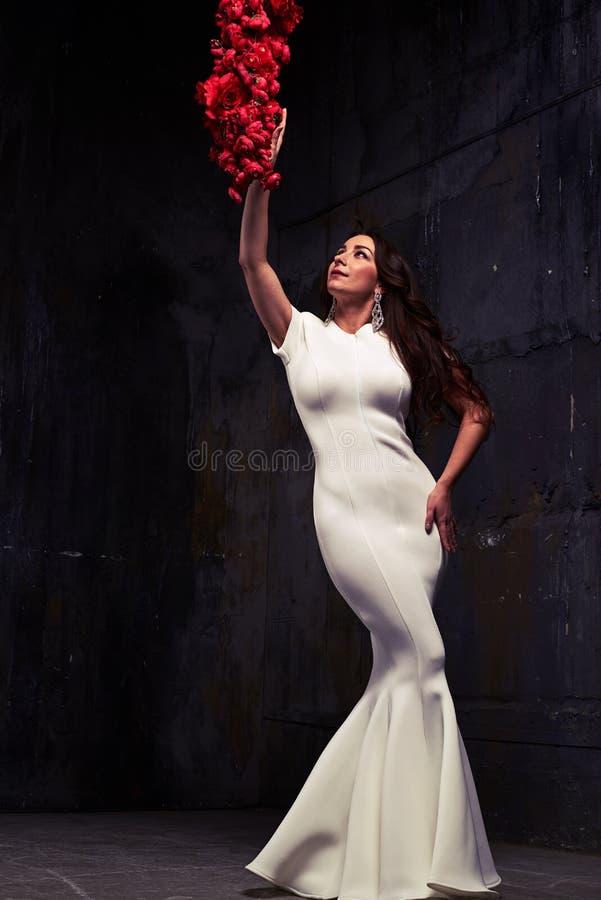 O baixo ângulo disparou da mulher impressionante no toque branco do vestido de noite imagens de stock