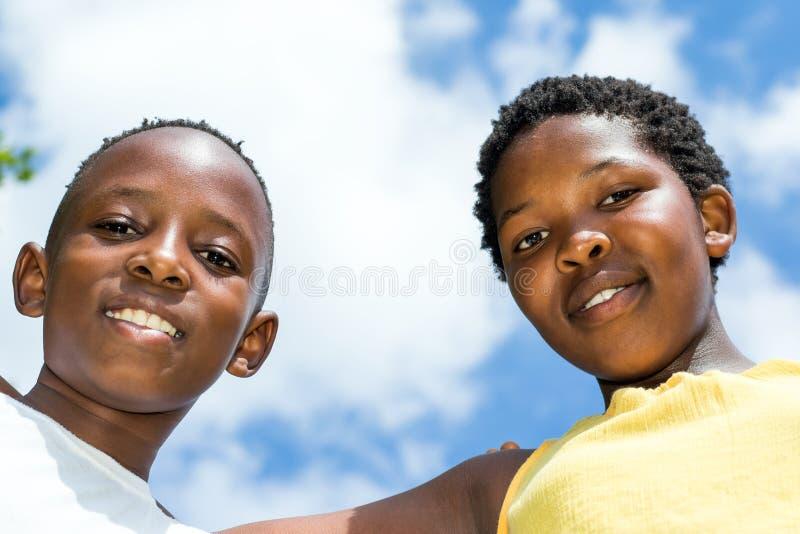 O baixo ângulo disparou de duas crianças africanas fora imagens de stock