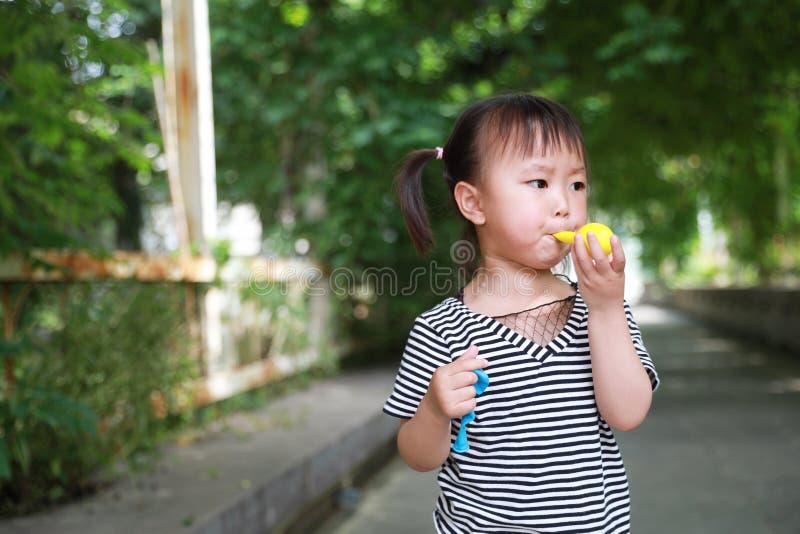 O balão chinês do sopro do riso do sorriso da criança da menina bonita bonito pequena feliz tem o divertimento na infância da fel fotos de stock