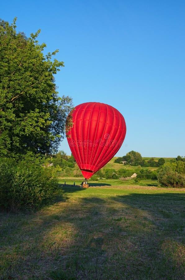 O balão de ar quente aterrou no campo na vila entre pitoresco os montes Céu azul claro sem nuvens, durante o por do sol imagens de stock