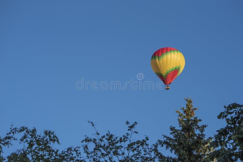 O balão de ar quente brilhante voa em um céu azul claro imagens de stock royalty free