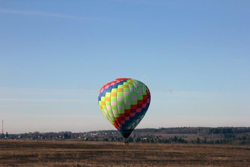 O balão multi-colorido bonito aterra em um campo na manhã, fotos de stock royalty free