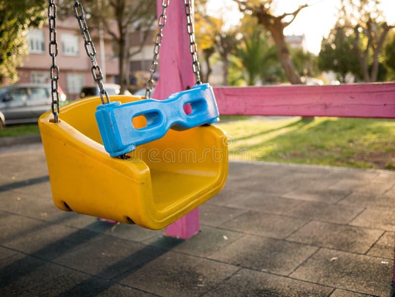 O balanço colorido ajustou-se no campo de jogos em um parque foto de stock