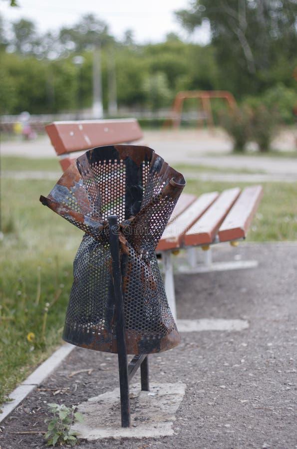 O balde do lixo ? danificado, quebrado no parque perto do banco vandalism imagem de stock