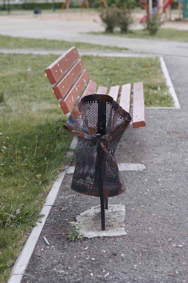 O balde do lixo ? danificado, quebrado no parque perto do banco vandalism imagem de stock royalty free