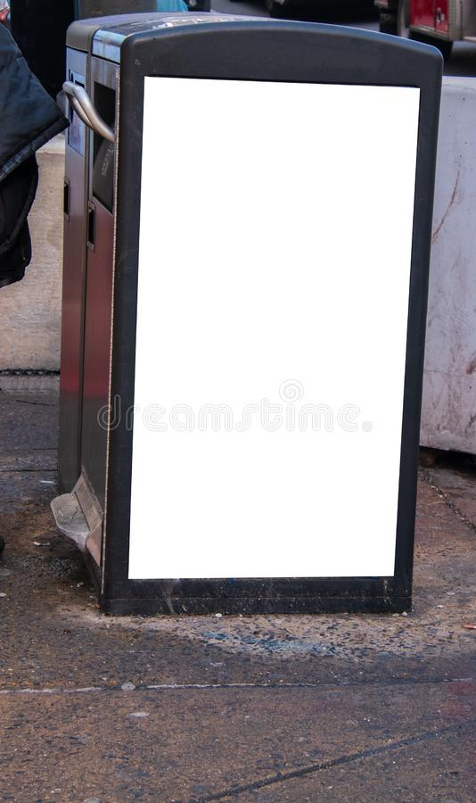 O balde do lixo em uma rua da cidade com um sinal vazio branco nele é lateral fotografia de stock