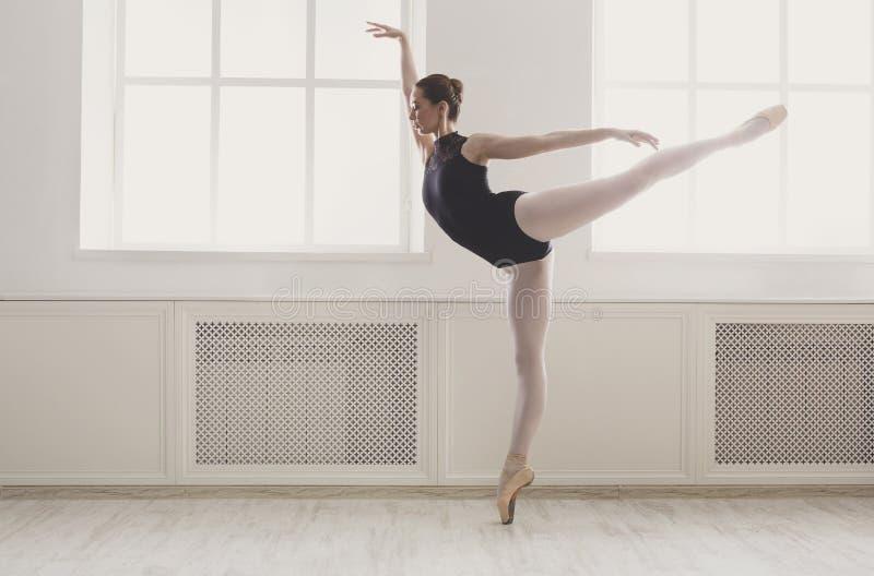 O ballerine bonito está na posição de bailado do arabesque imagens de stock