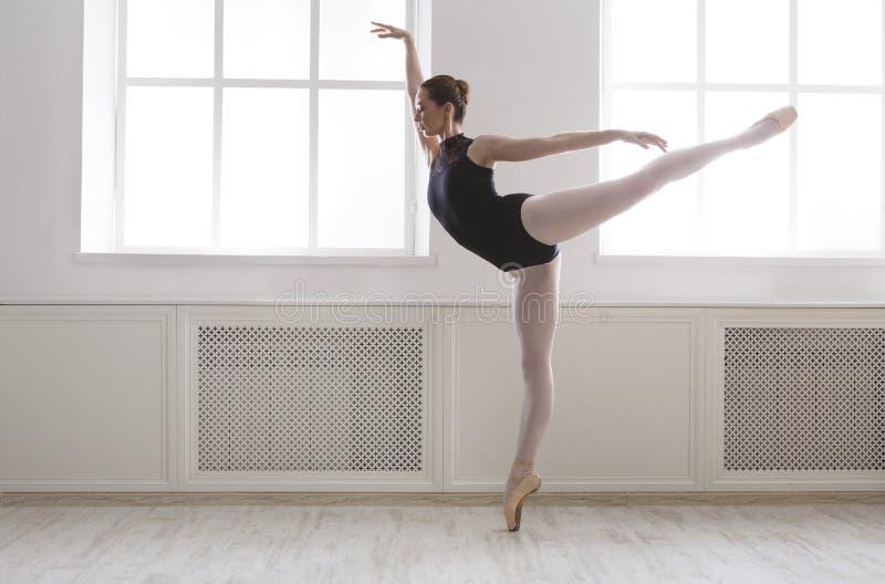 O ballerine bonito está na posição de bailado do arabesque imagem de stock royalty free