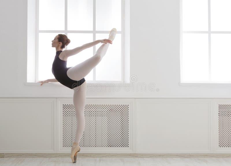 O ballerine bonito está na posição de bailado do arabesque fotografia de stock