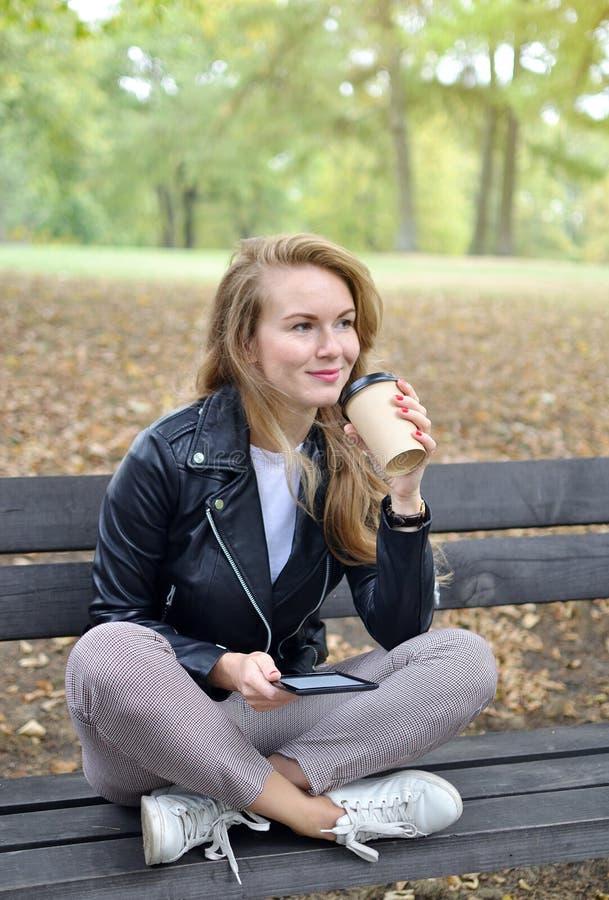 O banco de assento Autumn Park Reading da jovem mulher bonita um livro no dispositivo de Digitas relaxa o lazer foto de stock royalty free