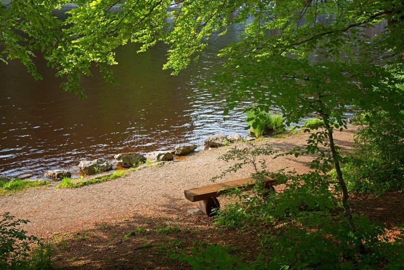 O banco de descanso na costa de uma amarração pond foto de stock royalty free