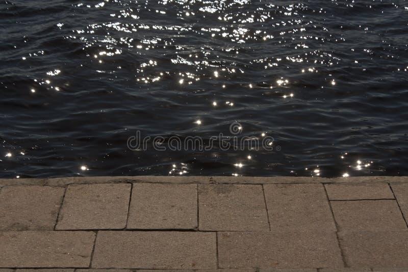 O banco de rio e o pavimento velho com sol irradiam-se imagem de stock