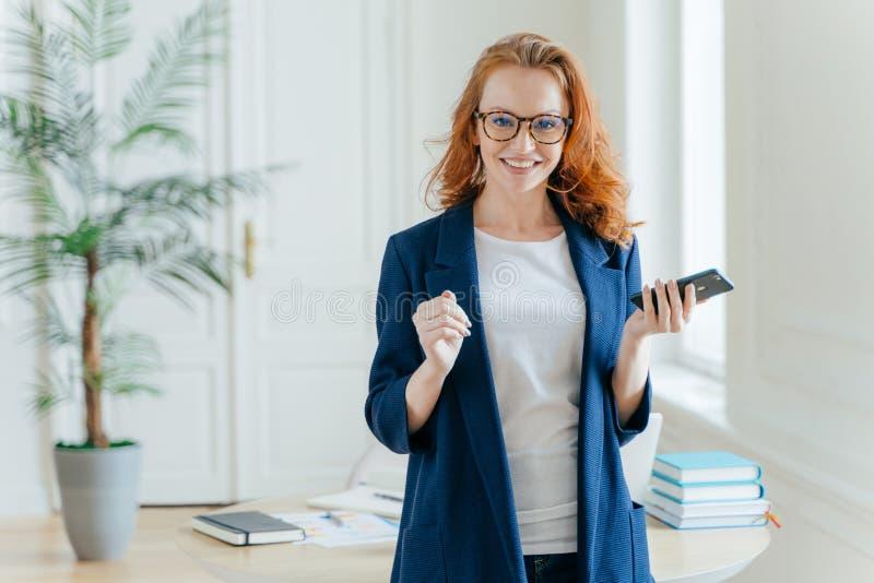 O banqueiro fêmea de sorriso do gengibre próspero faz o pagamento no servie em linha, espera a chamada importante, guarda o telef fotos de stock royalty free