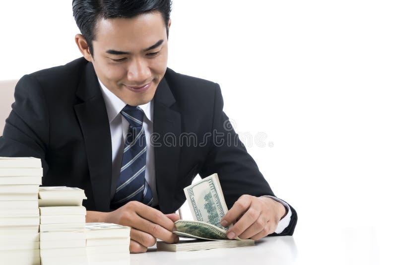 O banqueiro novo está contando cédulas no fundo branco e no c imagem de stock royalty free