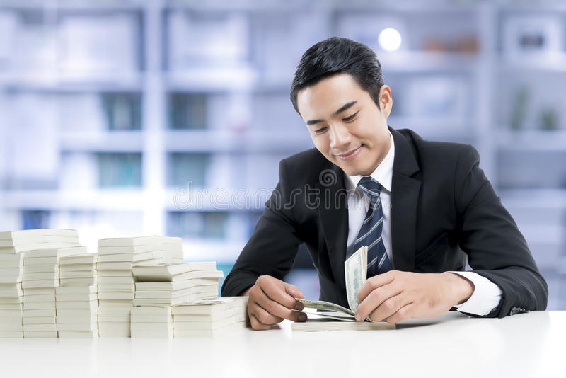 O banqueiro novo está contando cédulas no fundo do escritório do banco imagens de stock