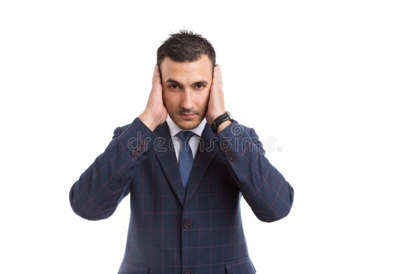 O banqueiro ou as vendas do homem de negócios equipam a coberta de suas orelhas foto de stock royalty free