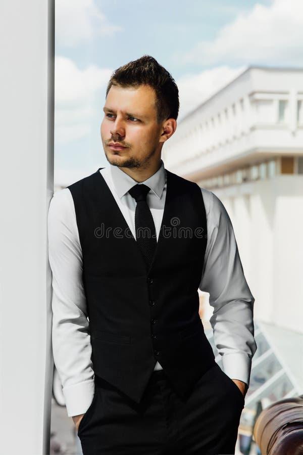 O banqueiro seguro do homem de negócios está inclinando-se na janela Mãos em uns bolsos, um terno da veste foto de stock