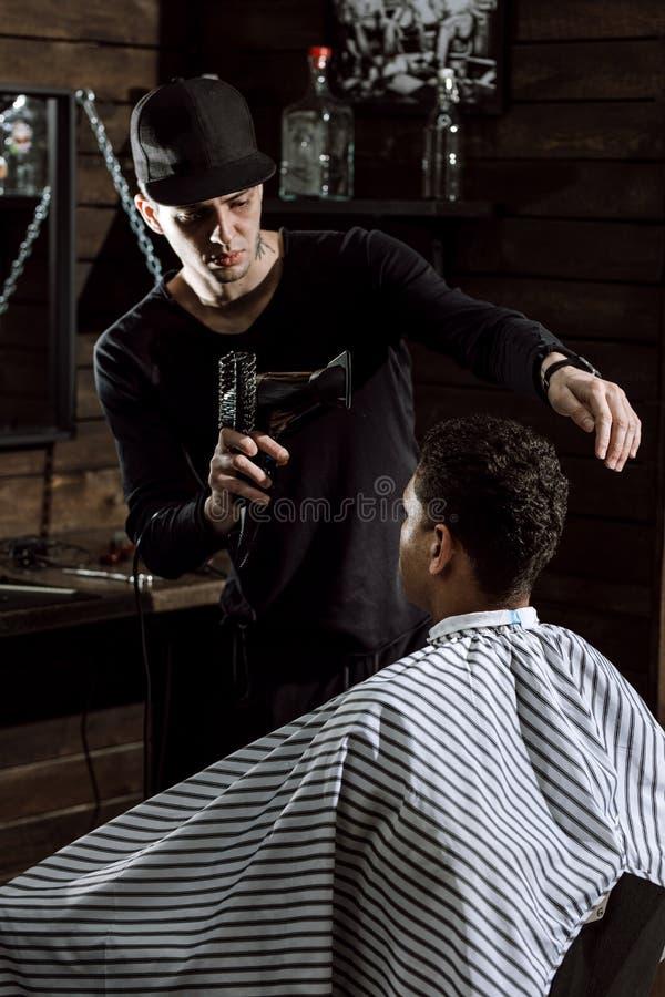 O barbeiro à moda vestido na roupa preta seca o cabelo do homem em um barbeiro imagem de stock royalty free