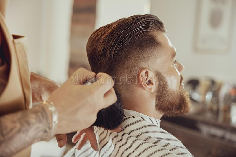 O barbeiro agita o cabelo fora do pescoço do ` s do cliente imagens de stock