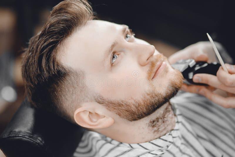 O barbeiro barbeia a barba do cliente no barbeiro dos homens com lâmina foto de stock royalty free