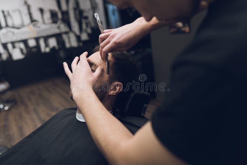 O barbeiro barbeia seus cabeça, bigode e barba ao homem no barbeiro imagens de stock royalty free