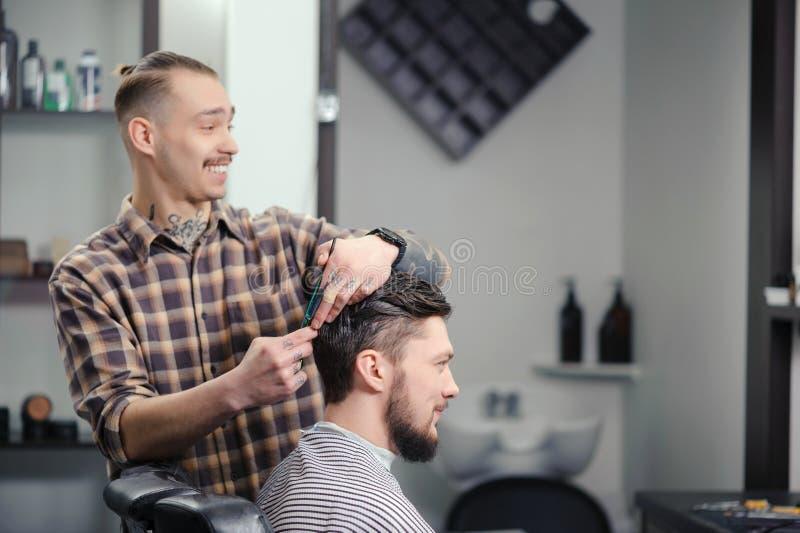 O barbeiro corta o cabelo de um homem imagens de stock royalty free