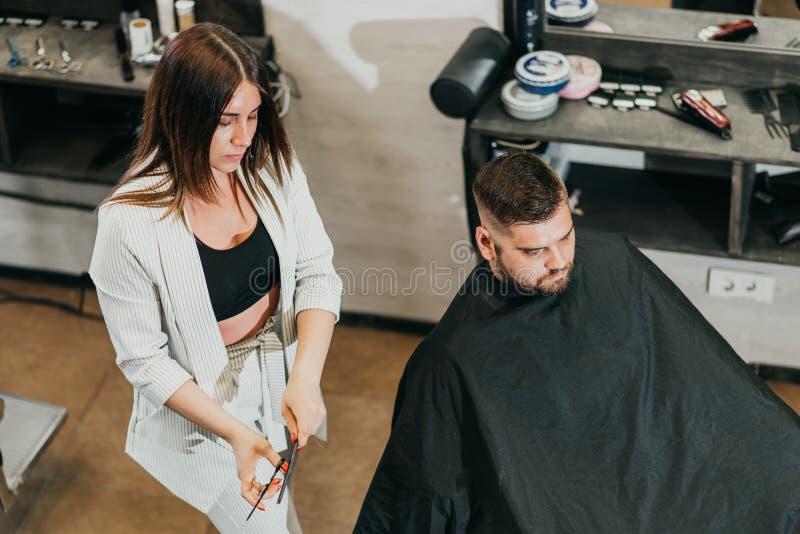 O barbeiro corta um homem farpado com as tesouras no sal?o de beleza imagens de stock royalty free