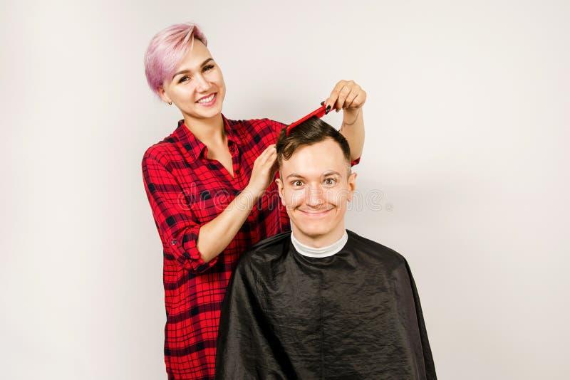 O barbeiro cortou o cabelo, o pente e o homem novo das barbeações em um fundo branco Retrato ascendente próximo de um indivíduo e fotos de stock