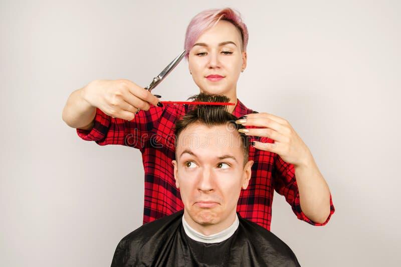 O barbeiro cortou o cabelo, o pente e o homem novo das barbea??es em um fundo branco Retrato ascendente pr?ximo de um indiv?duo e foto de stock royalty free