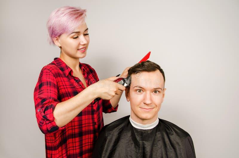O barbeiro cortou o cabelo, o pente e o homem novo das barbea??es em um fundo branco Retrato ascendente pr?ximo de um indiv?duo e foto de stock