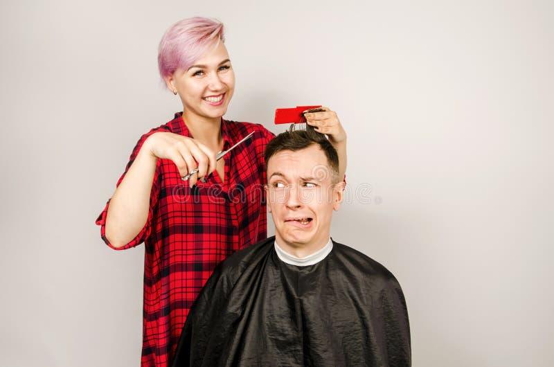 O barbeiro cortou o cabelo, o pente e o homem novo das barbea??es em um fundo branco Retrato ascendente pr?ximo de um indiv?duo e fotos de stock royalty free