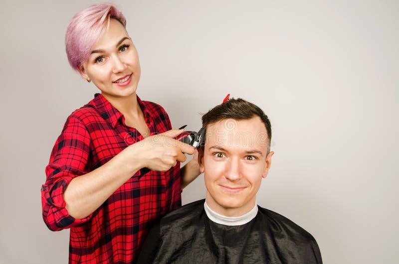 O barbeiro cortou o cabelo, o pente e o homem novo das barbea??es em um fundo branco Retrato ascendente pr?ximo de um indiv?duo e imagem de stock royalty free