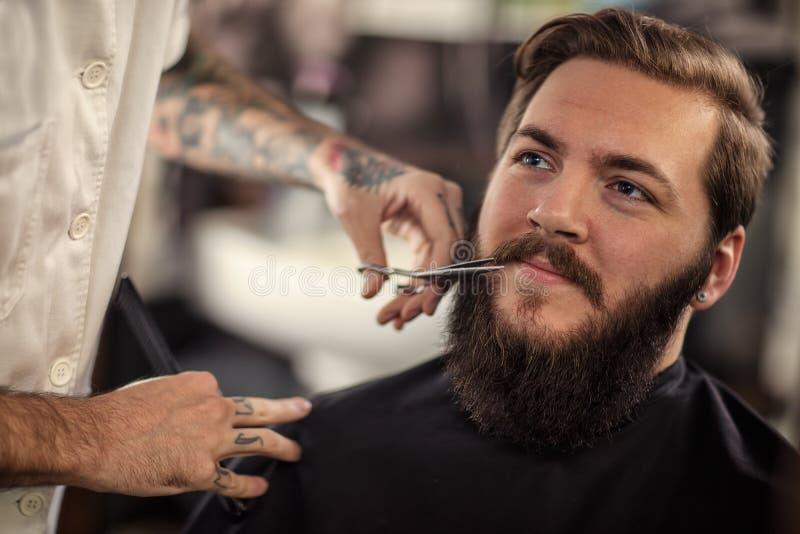 O barbeiro do homem com tesouras cortou o bigode foto de stock