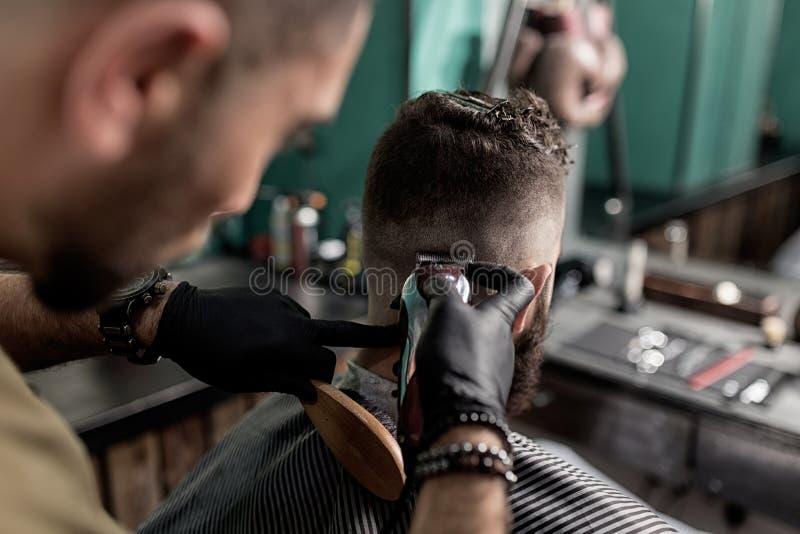 O barbeiro em luvas pretas barbeia os cabelos do homem na parte traseira em uma barbearia fotos de stock royalty free