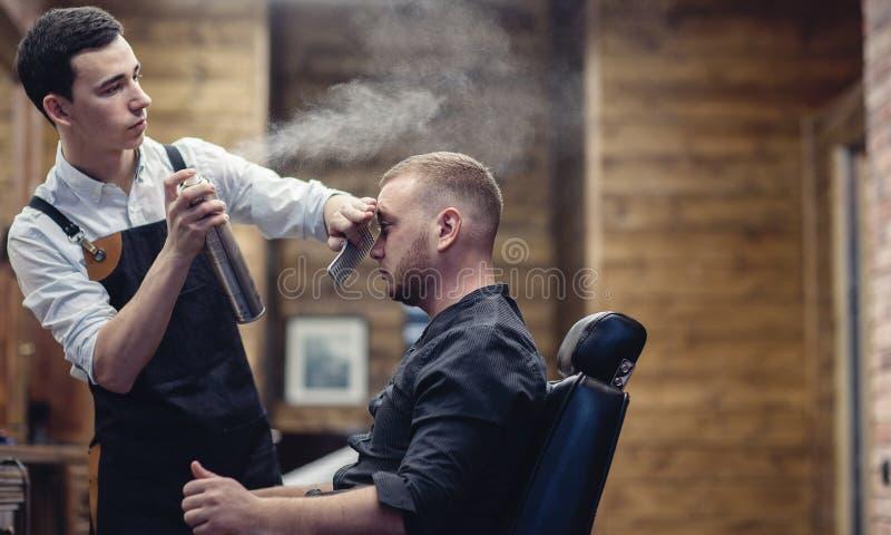 O barbeiro espirra a água no cabelo do cliente fotos de stock royalty free