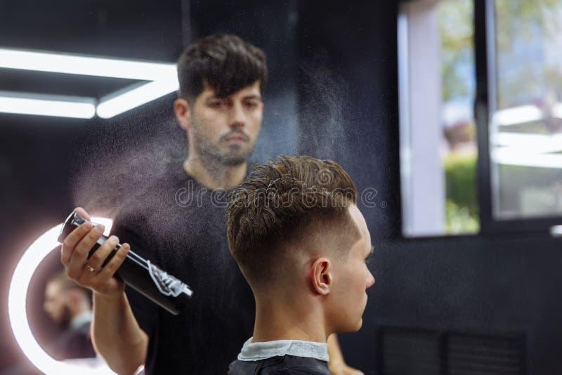 O barbeiro faz o cabelo que denomina com pulverizador de cabelo após o corte de cabelo na barbearia Homem caucasiano consider?vel imagens de stock royalty free