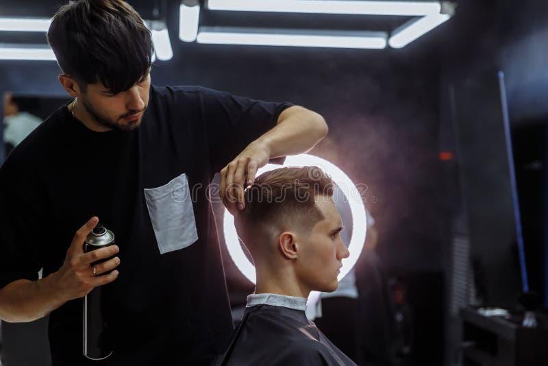 O barbeiro faz o cabelo que denomina com pulverizador de cabelo após o corte de cabelo na barbearia Homem caucasiano consider?vel fotografia de stock royalty free