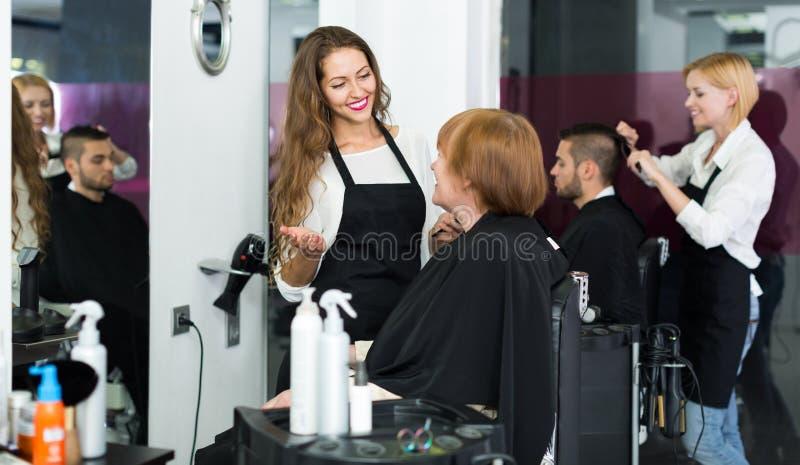 O barbeiro faz para cortar para a mulher fotografia de stock
