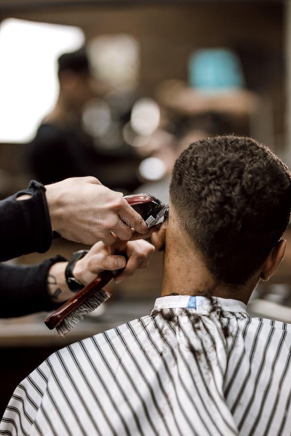 O barbeiro faz uma parte traseira e lados do cabelo do corte de lâmina para um homem preto-de cabelo à moda que senta-se na poltr imagem de stock