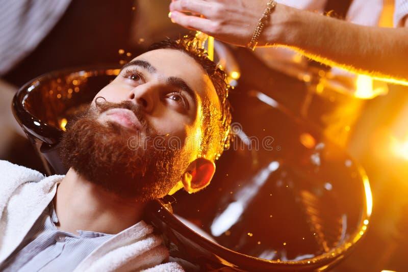 O barbeiro ou o cabeleireiro lavam a cabeça do cliente fotografia de stock royalty free