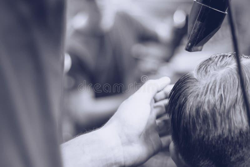 O barbeiro penteia o cliente do cabelo fotografia de stock royalty free