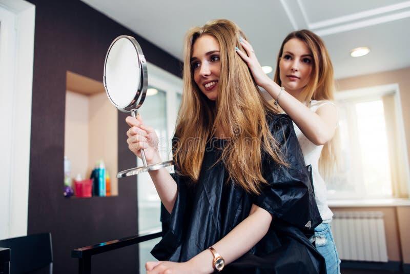 O barbeiro profissional novo terminou o corte de cabelo e mostra o resultado ao cliente que olha no espelho que senta-se dentro imagens de stock royalty free