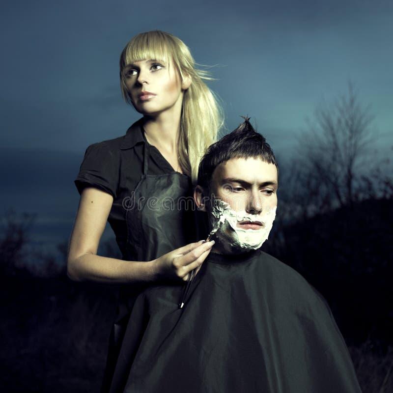 O barbeiro raspa o cliente fotografia de stock