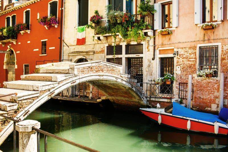 O barco amarrado ao lado da casa e da ponte coloridas Canais em Veneza, Itália imagem de stock royalty free