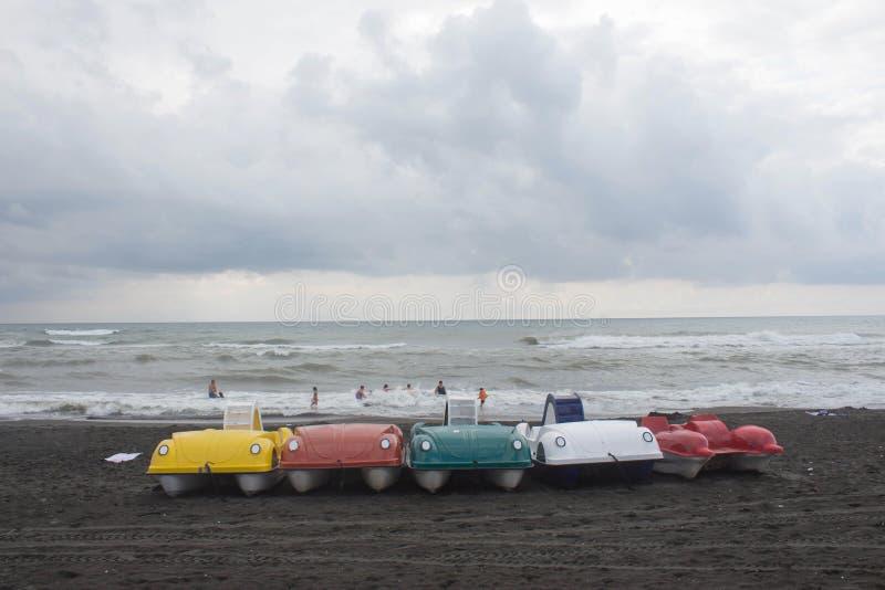 O barco colorido na praia, nublado, nuvens do pedal do pedalo, acena foto de stock royalty free
