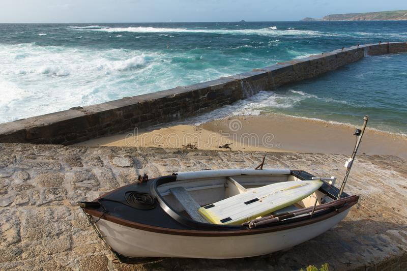 O barco de enfileiramento de Cornualha da angra de Sennon e a parede do porto com mar azul e branco acenam imagens de stock