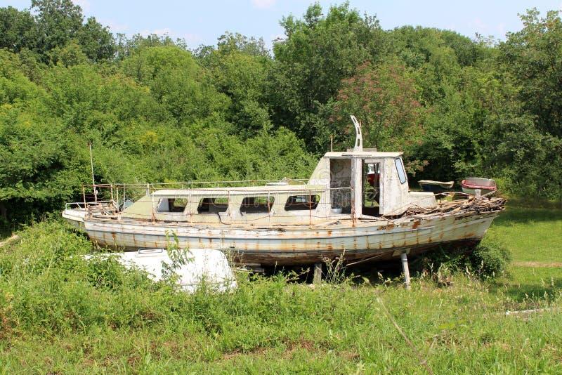 O barco de madeira dilapidado velho abandonado saiu no quintal entre a grama sem cortes e a vegetação de floresta fotos de stock royalty free