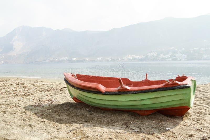 O barco de motor grego da plataforma aberta da pesca entrou no litoral arenoso da ilha de Telendos foto de stock